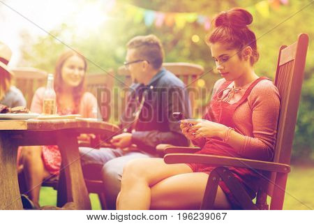 leisure, holidays, people and technology concept - young woman or teenage girl texting on smartphone and friends having dinner at summer garden party