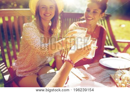 leisure, holidays, eating, people and food concept - happy friends having dinner at summer garden party and clinking drinks