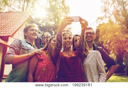 leisure, party, technology, people and holidays concept - happy friends taking selfie with smartphone at summer garden