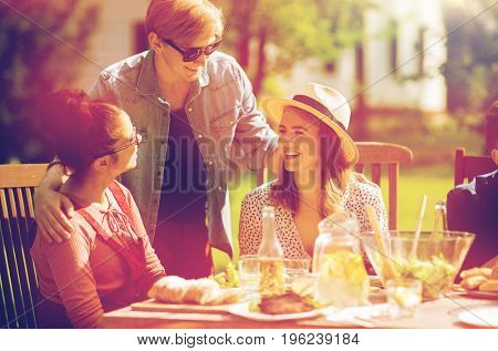 leisure, holidays, communication, people and concept - happy friends having dinner at summer garden party