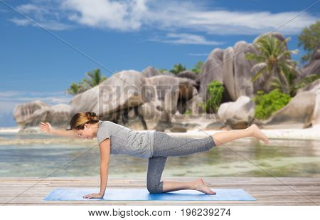 fitness, sport and healthy lifestyle concept - woman doing yoga in balancing table pose on mat over exotic tropical beach background