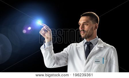 science, future technology and people concept - doctor or scientist in white coat with light over black background