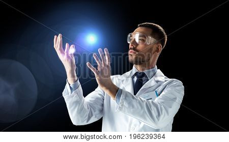 science, future technology and people concept - male doctor or scientist in white lab coat and safety glasses with light over black background