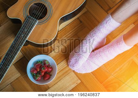 On the parquet floor guitar, a cup of strawberries, female feet in pink socks.