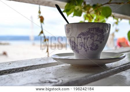 Cup of tea whit silver spoon and plate on a wooden bench
