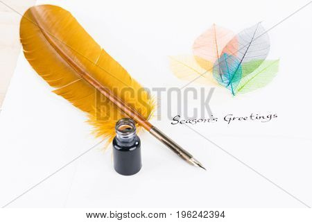 Season's Greetings wording with quill pen and leaves on cotton paper background