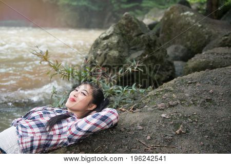 Pretty Asian traveler woman lying in happiness on a rock of waterfall.
