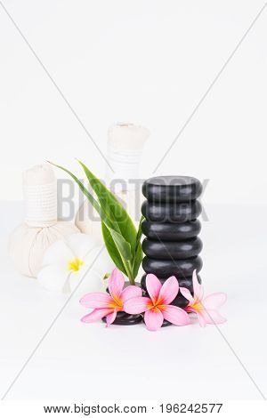 Traditional spa with herbal compress balls, hot stones and Frangipani flowers on white background