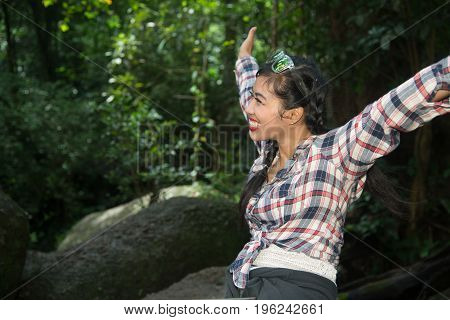 Pretty Asian traveler woman sitting in happiness on a rock in forest.