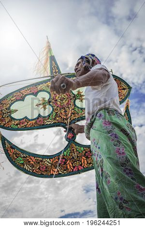 Kampung Mek Mas Kota Bahru Kelantan / Malaysia - July 15 2017 : A low angle shot of an elder waiting for the right moment to fly his uniquely design kite.