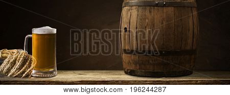 Beer barrel with beer glasses on table on wooden background.