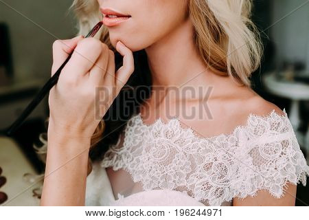 Young beautiful bride applying wedding make-up by make-up artist. Morning preparation before wedding. Close-up hands near face