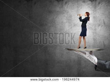 Hand of waiter presenting on tray woman playing flute