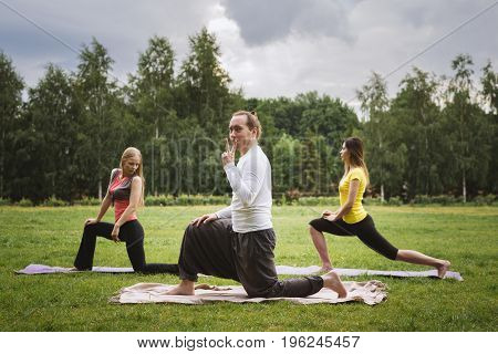 Yoga instructor posing during classes with a group of girls, summer