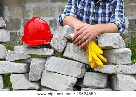 Builder in a plaid shirt. Helmet and stonework.Builder on the background of masonry construction.