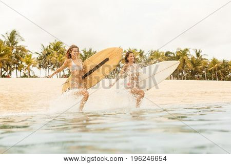 Two Beautiful Surfer Girls At The Beach Go Into The Water.