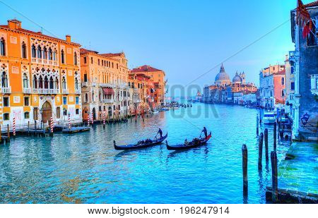 Grand Canal illuminated in sunset light and gondolier transporting tourists by gondola in Venice - Italy