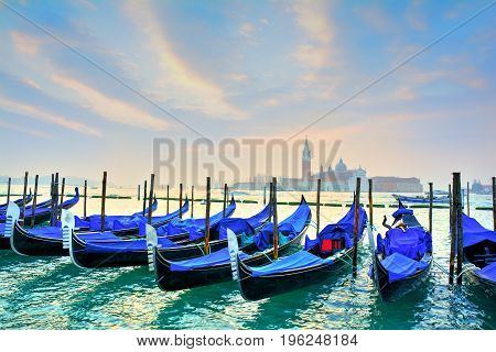 Gondolas on the famous Grand canal at sunrise, in Venice Italy