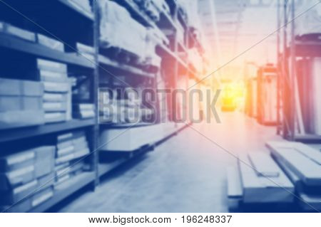 Blurred background warehouse is blue with spot of light flare. Concept interior modern logistics space. Copyspace