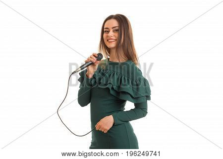 Cheerful woman in green color dress with microphone in hands isolated on white background