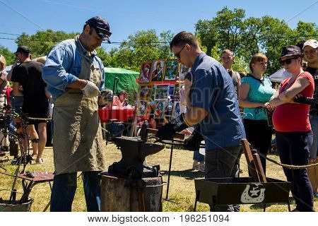 Experienced Blacksmith Teaches The Craft Of A Young Man