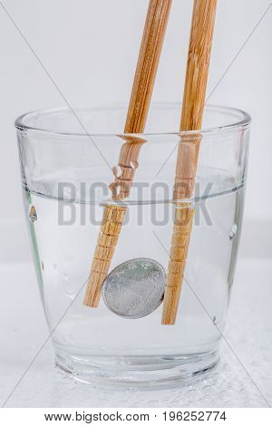Japanese coin (yen) holding by wooden chopsticks in a glass of water isolated on white background currency exchange concept.