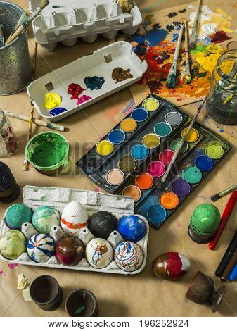 Photo of a messy table filled with egg decorating materials for making Easter eggs.