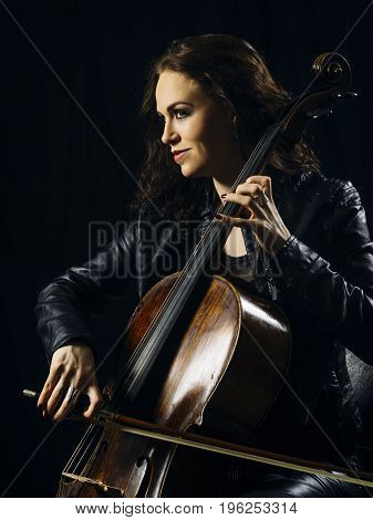 Photo of a beautiful woman playing her old cello.