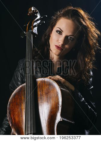 Photo of a beautiful woman posing with her old cello.
