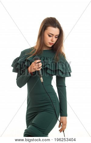 Charming woman in dress with microphone in hands isolated on white background