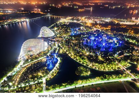 Beautiful top view of fantastic garden by Marina Bay in Singapore at night. Scenic ships with glowing lights in the sea are visible in background. Singapore is a popular tourist destination of Asia.