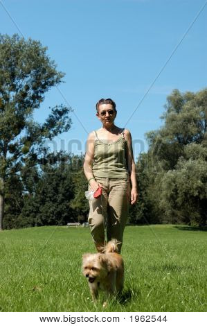 Senior woman walks her dog in a park poster