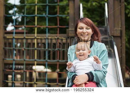Young mother happily spending time with a young child in a summer park