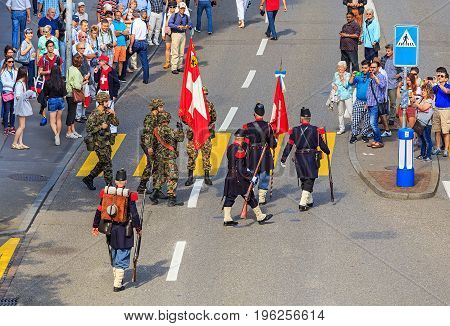 Zurich, Switzerland - 1 August, 2016: participants of the parade devoted to the Swiss National Day passing along Uraniastrasse street. The Swiss National Day is the national holiday of Switzerland, celebrated on 1 August.
