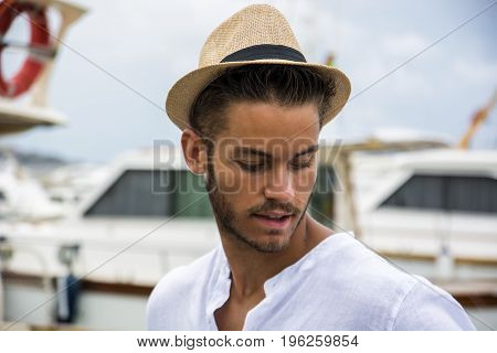 Portrait of handsome young man wearing light brown hat looking calmly away against of harbor with boats