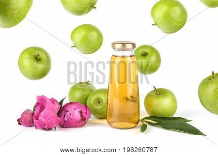Apple golden juice in bottle. Fruit soft drink in a glass bottles isolated on white background. Pink flowers peonies and flying apples