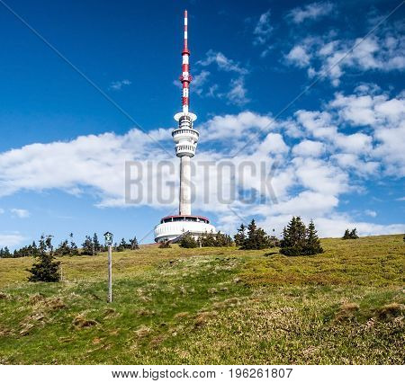 Praded hill in Jeseniky mountains with communication tower mountain meadow isolated small trees and blue sky with clouds