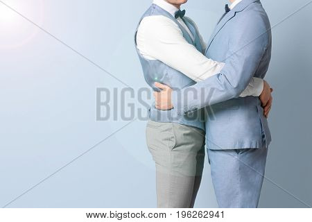 Gay couple embracing on color background