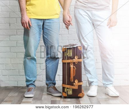 Gay couple with suitcase, passports and tickets on brick wall background