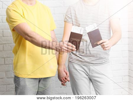 Gay couple with passports and tickets on brick wall background