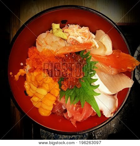 Delicious mix of raw fish straight from the market in Japan. Fish includes salmon tuna fish roe eggs shrimp and crab with wasabi. With a vignette.
