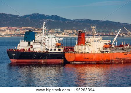 Black and Orange Tankers Tethered near Gibralter