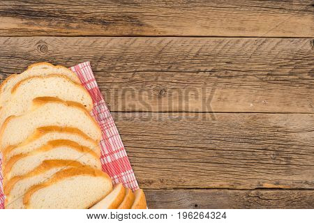 Loaf of bread on a wooden table. Top view.