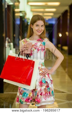 Shopping. Young beautiful blonde woman with some shopping bags in the mall