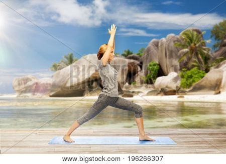 fitness, people and healthy lifestyle concept - happy woman doing yoga warrior pose on mat over exotic tropical beach background