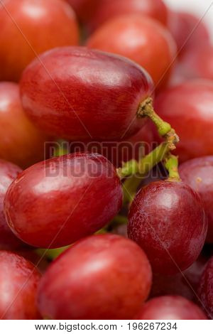 Red grapes. Soft close up of juicy healthly snacking fruit. Five a day vegetarian diet background image.