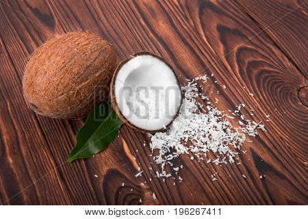 A pair of refreshing tropical coconuts on a wooden table background. Tasteful coconuts with fresh green leaves and white flakes. Summer ingredients for vegetarian dishes.