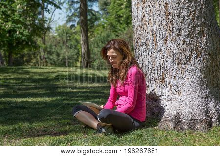 smiling adult woman with pink sweater watching digital tablet sitting in grass next to tree in park of Retiro in Madrid Spain