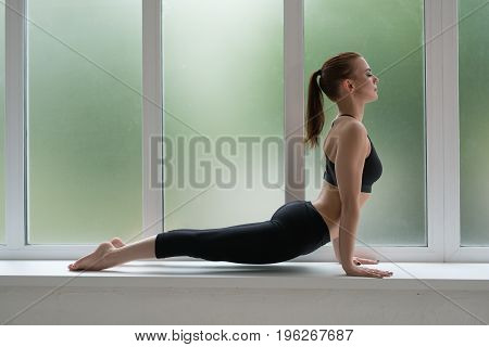 Young sexy fitness model in sports top and leggings posing in profile on window sill studio shot