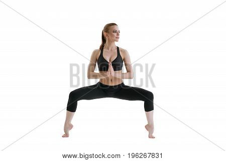Young sexy fitness model in sports top and leggings staying in balancing position isolated studio shot